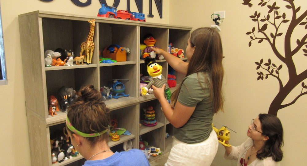 Lab personnel putting toys away